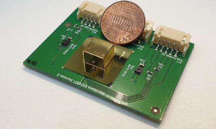 微型全超材料光学气体传感器(金色封装),旁边为一美分硬币