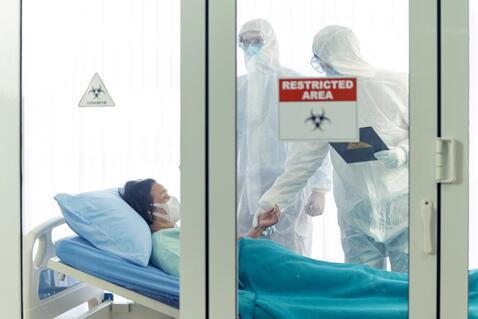 身穿个人防护用品的医生在隔离病房为 COVID-19患者做健康检查